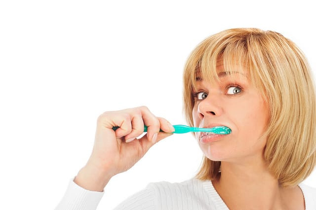 Detail portrait of a happy mature woman brushing her teeth