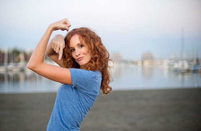 A woman jokingly shows off her muscles on a beach in Marina Del Rey, Calif.