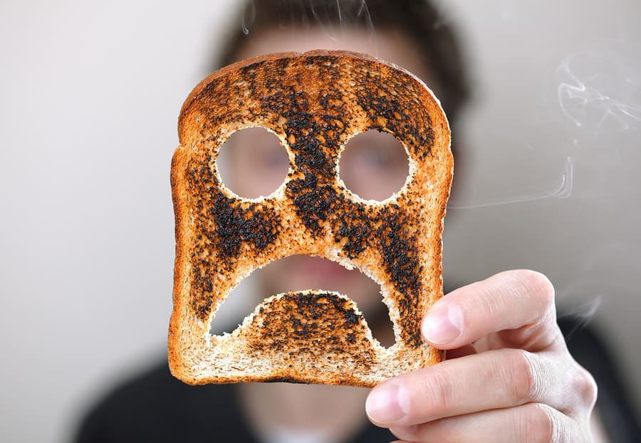 Man holding up a burnt slice of toast with an unhappy smiley con
